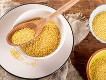 Semillas orgánicas del mijo en la tabla de madera rústica Imagen de archivo