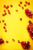 Semillas orgánicas maduras del pomergranate y del granate en fondo amarillo Foto de archivo libre de regalías