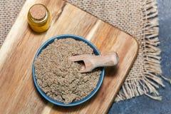 Semillas picaditas de un marianum y de un aceite del Silybum del cardo de leche en el escritorio de madera imagen de archivo