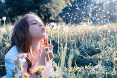 Semillas que soplan de la muchacha adolescente de un diente de león de la flor en parque de la primavera Foto de archivo