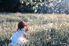 Semillas que soplan de la muchacha adolescente de un diente de león de la flor en parque de la primavera Imágenes de archivo libres de regalías