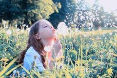 Semillas que soplan de la muchacha adolescente de un diente de león de la flor en parque de la primavera Fotografía de archivo