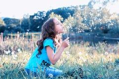 Semillas que soplan de la muchacha adolescente de un diente de león de la flor en parque de la primavera Imagen de archivo libre de regalías