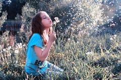 Semillas que soplan de la muchacha adolescente de un diente de león de la flor en parque de la primavera Foto de archivo libre de regalías