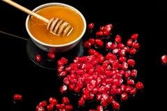 Semillas y miel frescas de la granada en un fondo negro Imagenes de archivo