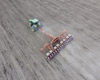 Semina del cereale Trattore con una seminatrice sul campo Facendo uso di un seme Fotografie Stock