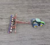 Semina del cereale Trattore con una seminatrice sul campo Facendo uso di un seme Fotografia Stock