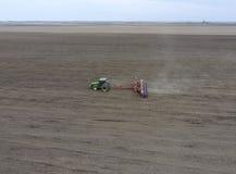 Semina del cereale Trattore con una seminatrice sul campo Facendo uso di una seminatrice per la piantatura del cereale Immagine Stock Libera da Diritti