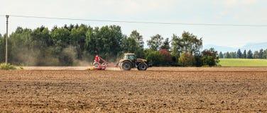Semina del trattore sul campo vuoto, piccoli alberi nel fondo Ampia insegna di agricoltura immagine stock