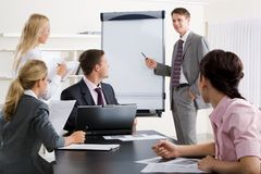 Seminar. Image of smart business people looking at their leader while he explaining something on whiteboard during seminar Royalty Free Stock Photo