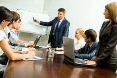 Seminar. Image of smart business people looking at their leader while he explaining something on whiteboard during seminar Stock Photos