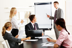 Seminar. Image of smart business people looking at their leader while he explaining something on whiteboard during seminar Royalty Free Stock Photography
