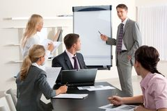 Seminar. Image of smart business people looking at their leader while he explaining something on whiteboard during seminar Royalty Free Stock Image