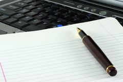 Pen, notepad and keyboard. Ballpoint pen resting on a lined notepad placed next to a laptop computer keyboard royalty free stock images