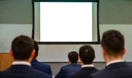 Seminar audience in class room. Blank white board, rear view. Young students listening to a lecture. Rear View of Audience People and blank white board, copy stock photos
