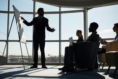 Seminar of business team. Confident men pointing at blank whiteboard at seminar Royalty Free Stock Images