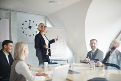 Seminar of economists. Mature coach standing by whiteboard and discussing financial graphs with group of managers or economists at seminar stock photography