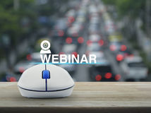 Seminar online concept. Webinar icon with wireless computer mouse on wooden table over blur of rush hour with cars and road, Seminar online concept Royalty Free Stock Photo