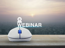 Seminar online concept. Webinar icon with wireless computer mouse on wooden table over modern city tower at sunset, vintage style, Seminar online concept Royalty Free Stock Image