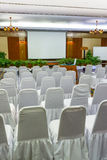 Seminar Room. Empty seminar room with covered chair, projector screen, stage, white board, stage and colourful carpet Royalty Free Stock Image