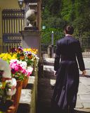 Seminarian walking past pots of blooming flowers royalty free stock photography