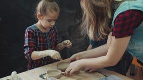 Seminarium för arbete med lera Mamman med två lilla döttrar är upptagen att modellera med lera gemensam kreativitet av föräldrar  stock video