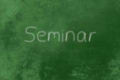 Seminarium på en svart tavla Arkivbild