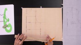 Seminarium till att sy Arbetsplats av sömmerskan: saxen blyertspenna, skissar och mäta bandet arkivfilmer