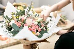 Seminariumblomsterhandlare och att göra buketter och blommaordningar Kvinna som samlar en bukett av blommor slapp fokus Royaltyfri Fotografi