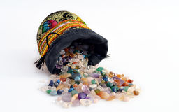 Semiprecious gems out of a sacket. Quartz and other semiprecious pebbles pouring out of a decorated sacket Stock Photography