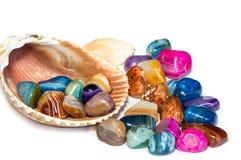 Semiprecious stubarwni agatów kamienie w lampasie z seashell na białym tle, Fotografia Stock