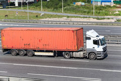 Semitrailer driving on highway with orange container Royalty Free Stock Photos