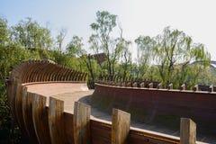 Semitubular wooden footbridge in air at sunny noon Royalty Free Stock Photo