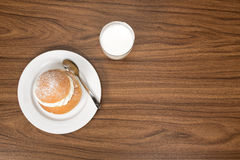 Semla with a glass of milk seen from above.