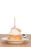 Semla mit einer brennenden Geburtstagskerze Stockbild