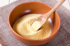 Semolina in a bowl with a wooden spatula. On a wooden background Stock Photo