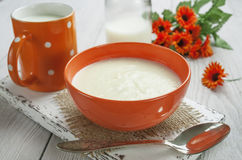 Semolina with butter. Semolina  in the orange bowl on the table Stock Photos