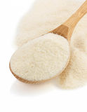 Semolina flour in spoon on white Stock Photos