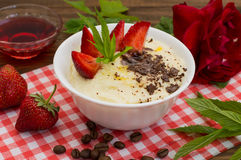 Semolina with grated chocolate and strawberry on a fabulously delicious tomorrow. Wooden background. Top view. Close-up. Semolina with grated chocolate and Royalty Free Stock Image
