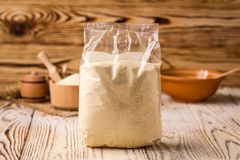 Semolina in packing and bowl on a wooden background. Healthy die. Tary cereals concept Royalty Free Stock Images
