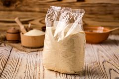 Semolina in packing and bowl on a wooden background. Healthy die. Tary cereals concept Stock Images