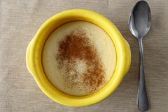 Semolina porridge with cinnamon. In a yellow saucepan stock image