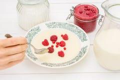 Semolina porridge with raspberries ,jar with milk and jam for breakfast. Semolina porridge with raspberries ,jar with milk , sugar and jam for breakfast on the Royalty Free Stock Image