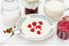 Semolina porridge with raspberries ,jar with milk and jam for breakfast. On the white wooden table, meal of wheat  milled grain Royalty Free Stock Photo
