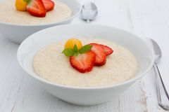 Semolina porridge. With strawberries and gooseberry Royalty Free Stock Photography