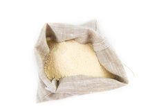 Semolina in a sack. Semolina grits in linen brown sack, isolated on white Stock Photo