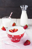 Semolina strawberry in red bowl on a fabric napkin on a white ta. Ble with milk Royalty Free Stock Photography