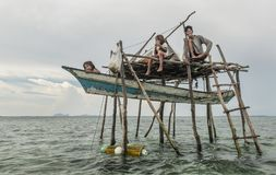 Father and his two daughters sitting outside their small tent house floating in Semporna sea, Sabah Semporna, Malaysia. Semporna, Malaysia June 2015: The Bajau Stock Photography