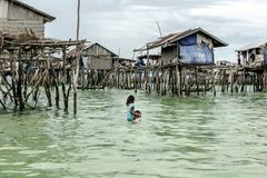 Bajau tribal girl carrying her brother to her home before he gets sunk in the sea, Sabah Semporna, Malaysia stock photo