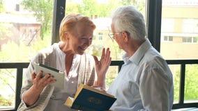 Sempre junto? Pares aposentados bonitos felizes que estão oposto a se e ao riso